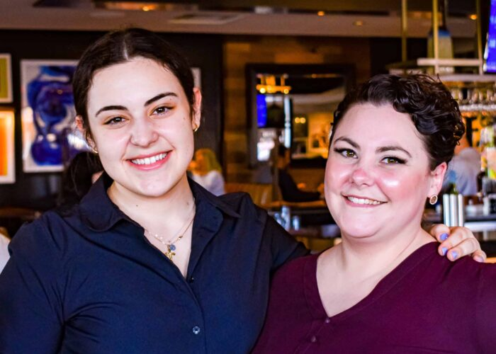 A server stands on the left with her arm around her manager. Both women are smiling.